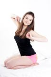 Girl stretching after a nap. Young beautiful girl sitting on the bed and stretches Stock Photography