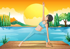 A girl stretching near the river Royalty Free Stock Photos