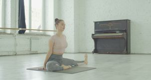 Girl stretching one leg toe-touch stretch exercise. Fitness sporty woman stretching one leg toe-touch stretch exercising hamstring and glute muscles stretches on stock footage