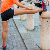 Girl stretching before running in city marathon Royalty Free Stock Image