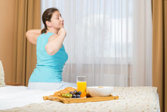 Girl stretching after sleep. Sitting on a bed Stock Images