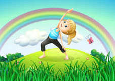 A girl stretching at the top of the hill with a rainbow Stock Images