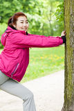 Girl stretching beside tree Stock Image