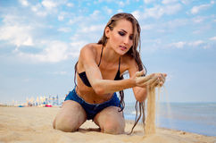 Girl strewing sand through her hands. Girl sitting on the beach and strewing sand through her hands stock images