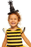 Girl in striped bee costume wearing spider hat Royalty Free Stock Photography