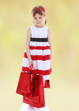 Girl in a striped dress holding red paper shopping Royalty Free Stock Image