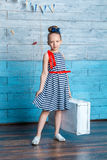 Girl in a striped dress holding  suitcase Royalty Free Stock Photo