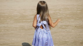 Girl in a striped dress and long hair dancing back. On the beach stock footage