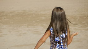 Girl in a striped dress and long hair goes on back. Along the beach stock footage