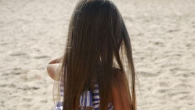 Girl in a striped dress and long hair goes on back. Along the beach stock video