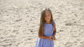 Girl in a striped dress and long hair walking along. The beach stock video footage