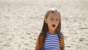 Girl in a striped dress and long hair walking along. The beach stock video