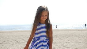 Girl in striped dress standing on the beach. And squints eyes stock footage