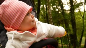 Girl in a striped hat. Smiling child in a hat looks away. Smiling girl. Happy, happy baby outdoors. Girl in a striped hat. beautiful child stock video footage