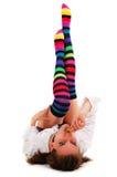 Girl in striped motley knee-length. Socks sucks lollipop isolated on white background Royalty Free Stock Photo
