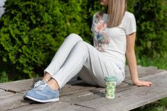 Girl in striped pants, blue sneakers and t shirt sitting on bench next to a cup of coffee resting in the park stock photos