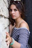 Girl in striped shirt by stone wall Stock Photo