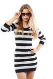 Girl in a striped sweater corrects sunglasses Royalty Free Stock Photo