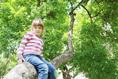 Girl in striped sweater sitting on tree trunk and looking Royalty Free Stock Image