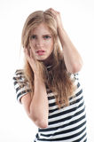Girl in a striped sweater straightens hair Royalty Free Stock Photography