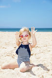 Girl in striped swimsuit on a white beach showing sandy hands Royalty Free Stock Images