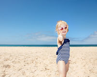 Girl in striped swimsuit on a white beach showing thumbs up Stock Photography