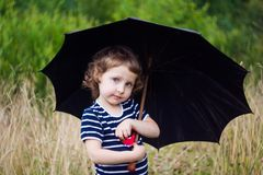 Girl in a striped T-shirt with a black umbrella in the field royalty free stock photo