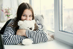 Girl in a striped T-shirt hugging a teddy bear lying on the wind Royalty Free Stock Photo
