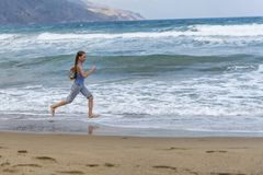 Girl in striped t-shirt running along the beach stock images