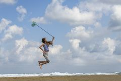 Girl in a in striped t-shirt on the sea catches clouds royalty free stock photos
