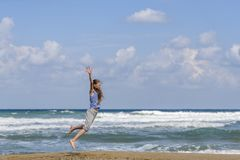 Happy young woman jumping on the beach stock images