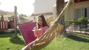 Girl in a striped T-shirt sitting in a hammock stock footage