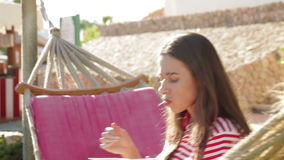 Girl in a striped T-shirt sitting in a hammock stock video footage