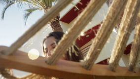 Girl in a striped T-shirt sitting in a hammock stock video