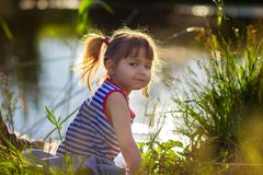 The girl`s portrait in a striped undershirt. The girl in a striped undershirt near the lake Stock Photography