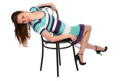Girl in stripy blue dress bend back on stool. Stock Images