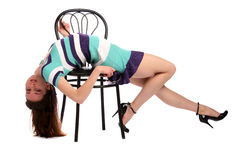 Girl in stripy blue dress bend down on stool. Royalty Free Stock Images