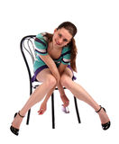 Girl in stripy blue dress on stool smiling. Royalty Free Stock Photography