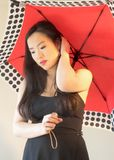 Girl strokes hair under bright red umbrella. Young Asian girl poses under a red umbrella as she adjusts her hair royalty free stock image