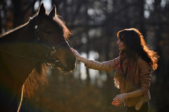 Girl stroking horse. Pretty girl, talking to her horse, hugging it, both looking happy and content Royalty Free Stock Photos
