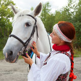 The girl stroking horse. The  girl in traditional Russian costume stroking horse Stock Photography
