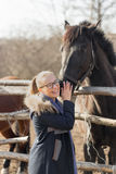 Girl stroking a thoroughbred horse in the pen for paddock Stock Images