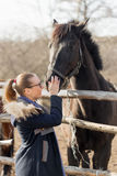 Girl stroking a thoroughbred horse in the pen for paddock Stock Photos