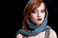 Girl with strong makeup. And scarf on her head, looking straight to the camera Royalty Free Stock Photography