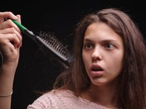 Girl struggling with tangled hair on the black background. Close-up woman looking at a comb with hair. Balding concept. A concerned, disgusted woman holding a stock photos