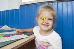 Girl stuck in the eye mosaic with the letter and smiles Royalty Free Stock Photo