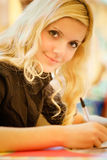 Girl-student. The young woman-student performs written work Royalty Free Stock Photos