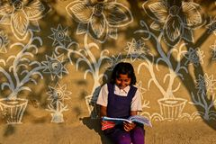 Girl Student. An adolescent girl reading a book infront of the painted wall in the rural area of West Bengal-India Stock Images