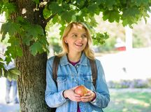 Girl student with backpack hold apple while stand near tree. Healthy snack. Students life concept. Take minute to relax. Break for snack. Student eat apple royalty free stock photos