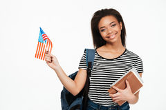 Girl student with backpack holding books and US flag Royalty Free Stock Image
